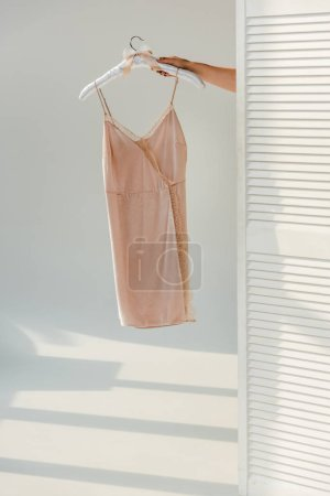 female hand holding hanger with silk nightie