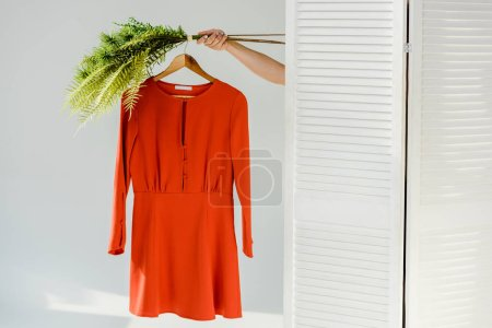 female hand holding hanger with red stylish dress and green plants near room divider