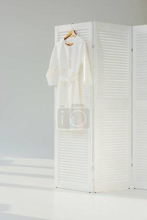 Photo for Elegant white dress hanging on wooden room divider - Royalty Free Image