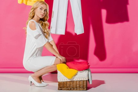 attractive woman sitting near wicker basket on pink