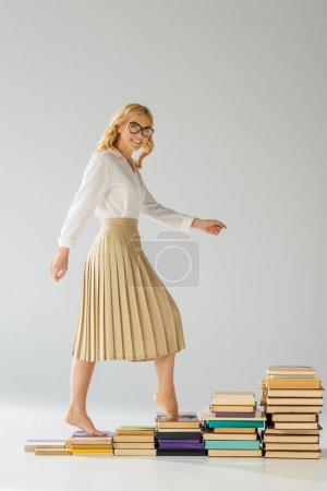 Photo pour Femme souriante dans des lunettes marchant sur des marches faites de livres - image libre de droit