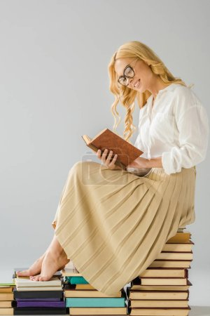 attractive smiling barefoot woman in glasses reading and sitting on books