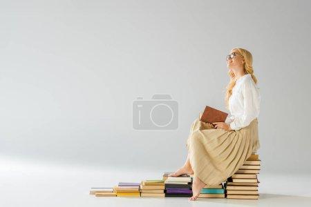 Photo pour Attrayant rêver femme pieds nus dans des lunettes assis sur des marches en livres - image libre de droit