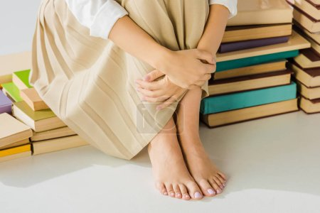 close up of barefoot woman sitting on pile of books