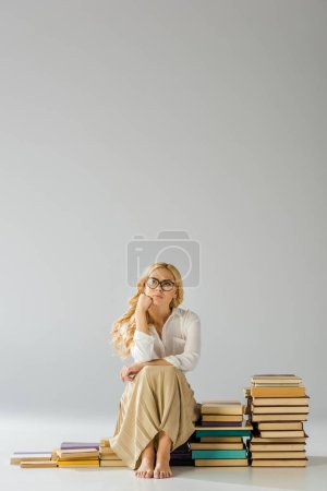 beautiful dreaming barefoot woman in glasses sitting on steps made of books