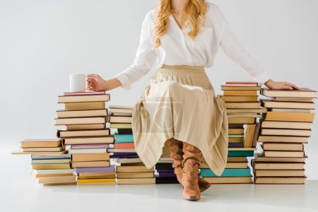 close up of adult woman sitting on pile of books with cup