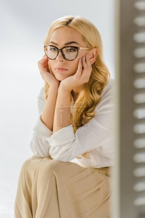 close up of adult thoughtful woman sitting near door isolated on grey