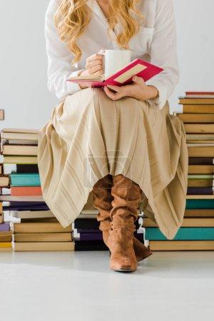 Photo pour Gros plan de femme buvant du café, lisant et s'asseyant sur une pile de livres - image libre de droit