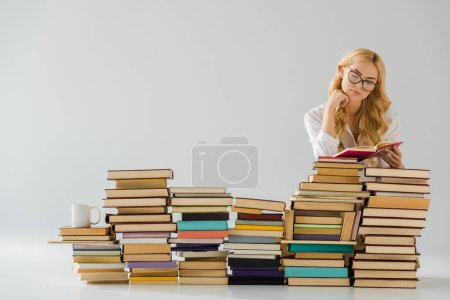 beautiful woman in glasses reading near pile of books