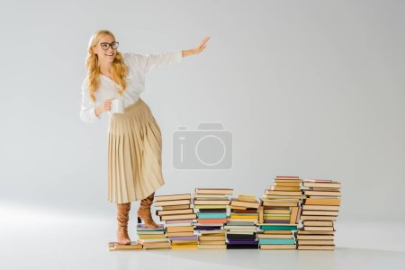 Photo for Adult stylish woman standing on books with white mug - Royalty Free Image