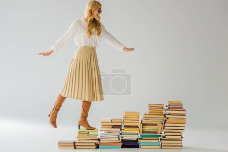 adult elegant woman balancing on vintage books