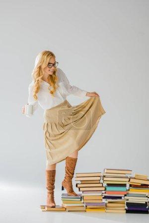 Photo pour Adulte élégante femme debout sur des livres avec tasse blanche - image libre de droit