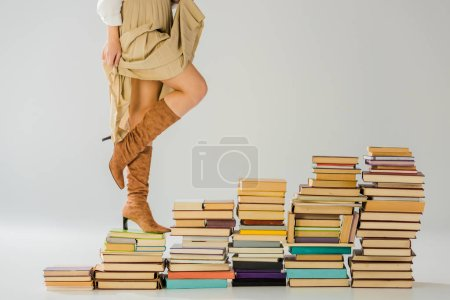 close up of woman in boots walking on vintage books