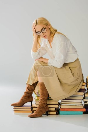 tired blonde woman in glasses sitting on pile of retro books
