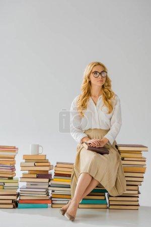 beautiful adult woman sitting on pile of retro books