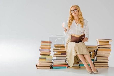 Photo for Beautiful adult woman sitting on pile of retro books with white cup - Royalty Free Image