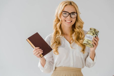 beautiful woman in glasses with book and savings in jar isolated on grey
