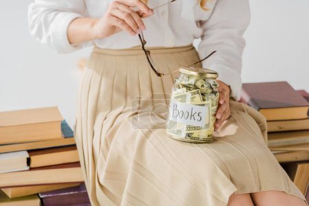 close up of woman sitting on books with money savings in jar