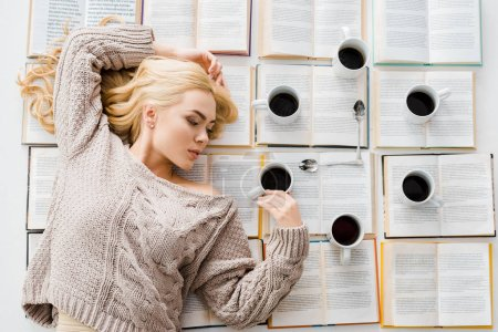 woman laying near clock made of white cups with coffee and spoons on open books