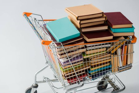 Photo for Pile of vintage books with multicolored covers in shopping cart isolated on grey - Royalty Free Image