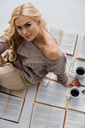 Photo for Close up of woman sitting on open books with coffee cups isolated on grey - Royalty Free Image