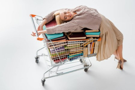 relaxed woman laying on pile of vintage books with multicolored covers in shopping cart isolated on grey