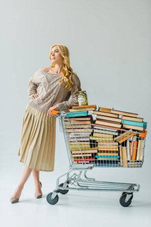 beautiful woman with money in jar and retro book in shopping cart isolated on grey