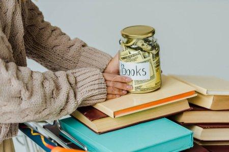 Photo pour Gros plan des mains féminines tenant le bocal avec de l'argent sur les livres - image libre de droit