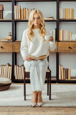 beautiful woman sitting with cup of coffee and reading book in living room