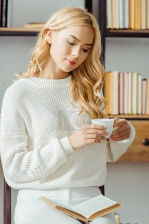 close up of beautiful woman sitting with cup of coffee and reading book in living room