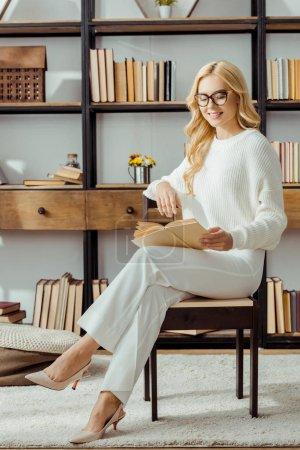 Photo pour Belle femme à lunettes assis et lisant livre dans le salon - image libre de droit