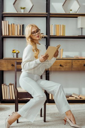 beautiful woman in glasses sitting in library and reading book