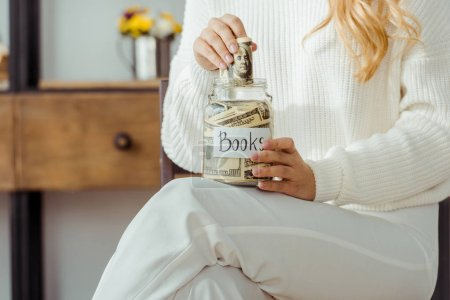 close up of woman holding glass jar with money savings