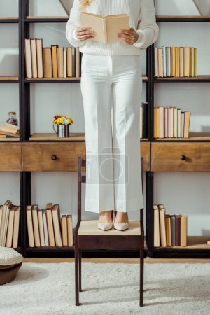 close up of adult woman standing on chair in living room and reading book