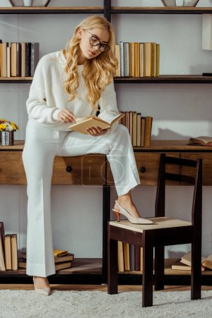 attractive woman in glasses sitting on rack and reading book in living room