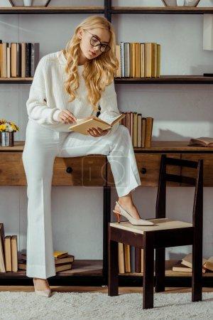 Photo pour Jolie femme à lunettes assise sur la grille et la lecture livre dans le salon - image libre de droit