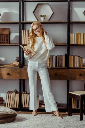 Photo pour Jolie femme à lunettes debout près de rack et livre dans le salon de lecture - image libre de droit