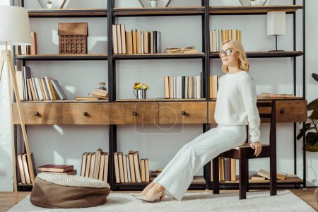adult blonde woman in glasses sitting near rack with books