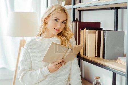 close up of beautiful woman reading book near rack