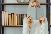 close up of blonde woman hiding face behind book