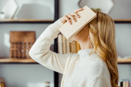 close up of blonde woman putting book on face