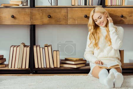 smiling woman sitting on floor and reading book in living room