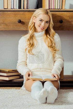 Photo pour Sourire de femme assise sur le plancher et le livre de lecture dans le salon - image libre de droit