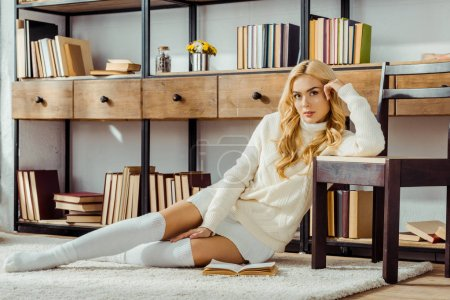 beautiful woman sitting on carpet with book in living room