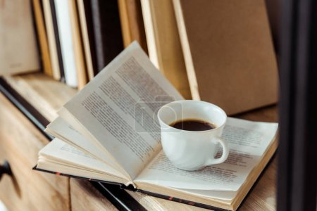 Photo pour Gros plan du livre ouvert avec une tasse de café sur l'étagère - image libre de droit