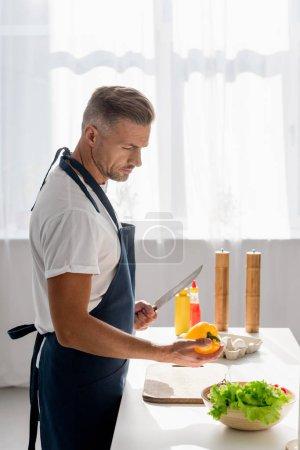 Handsome man preparing salad at home