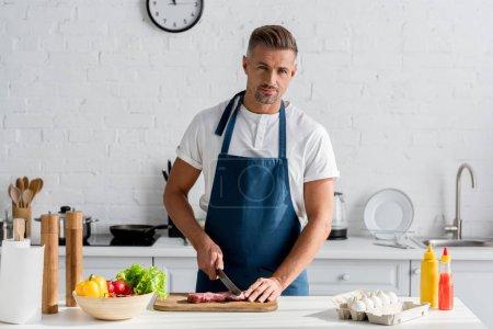 handsome man cutting pork meat on the kitchen