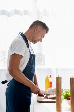 Mature man cutting meat for steak on a wooden board