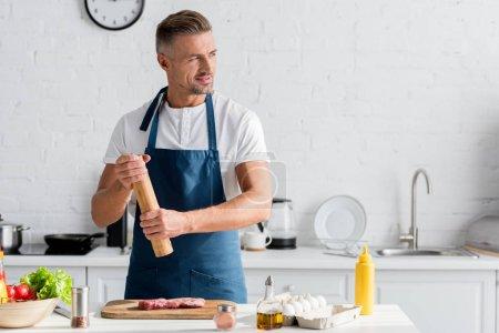 Photo for Smiling man enjoying cooking dinner in kitchen - Royalty Free Image