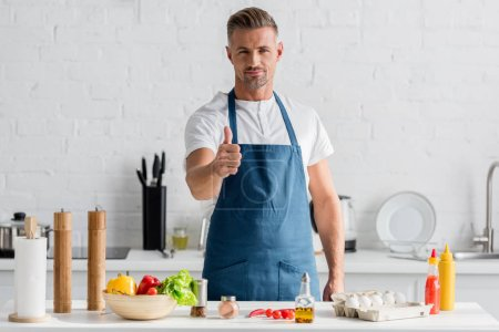 man in apron standing at kitchen and showing thumbs up sign